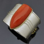A large cabochon of Pacific salmon colored coral set in sterling silver bracelet with 18k yellow gold accents. Photo courtesy of the artist, Darryl Dean Begay.